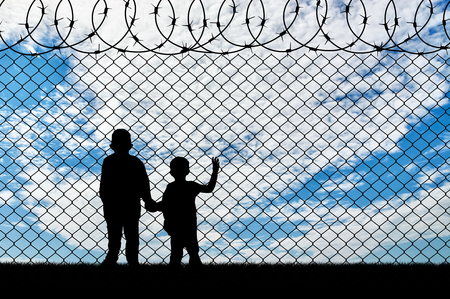 Refugee children concept. Silhouette of two children of refugees near the border fence of barbed wire 免版税图像