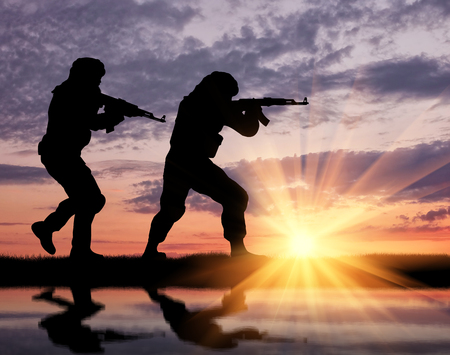 terrorists: Terrorism and conflict. Armed terrorists and theirs at sunset reflected in water