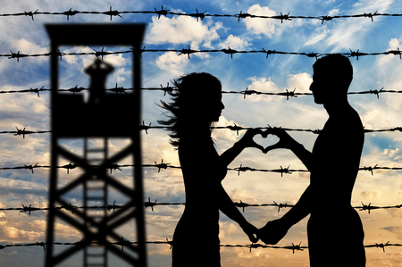 alzando la mano: Refugees concept. Male and female refugees show hands symbol heart on the background of the fence and watchtower