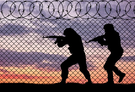 terrorists: Terrorism and conflict. Armed terrorists near the fence of barbed wire