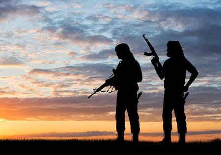 テロと紛争。夕暮れ時の 2 つの武装テロリスト