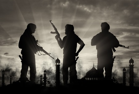 terrorists: Terrorism and conflict. Armed terrorists on the background of a mosque in the smoke Stock Photo