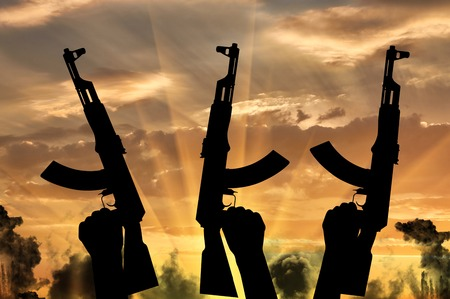 terrorists: Terrorists concept. Weapons in the hands of terrorists, against the background of a sunset in the smoke Stock Photo
