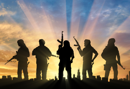 Terrorism and conflict. Armed terrorists near the city at sunset