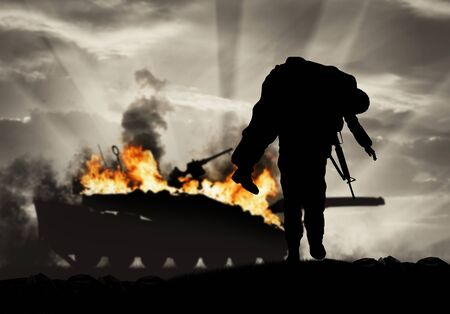 Concept of war and conflict. Soldier carries a wounded soldier on a background of a burning tank