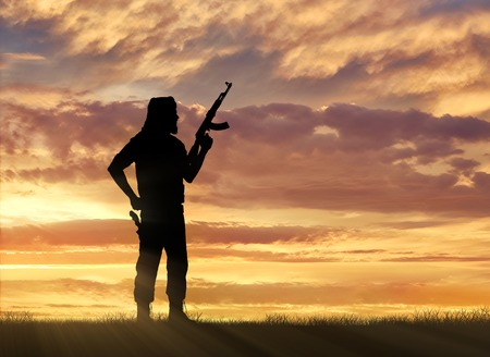 terrorists: Terrorism and conflict. Armed terrorists on the sunset background