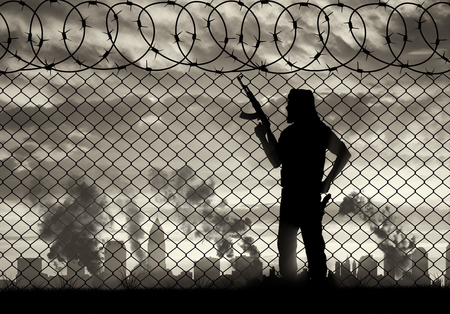 terrorists: Terrorism and conflict. Armed terrorists near the fence of barbed wire and the city in smoke