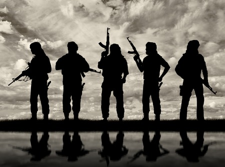 Terrorism and conflict. Armed terrorists and their reflection in water Stok Fotoğraf