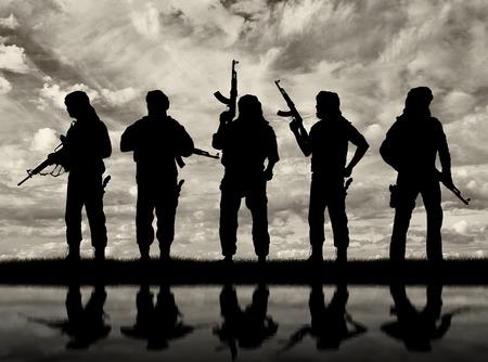 Terrorisme en conflict. Gewapende terroristen en hun weerspiegeling in het water Stockfoto