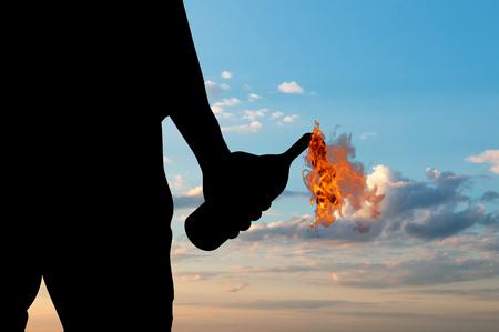 molotov: Terrorist concept. Silhouette of a terrorist holding a molotov cocktail at sunset background
