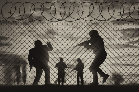 hostages: Terrorism concept. The terrorist attack against the background of the fence of barbed wire and smoke