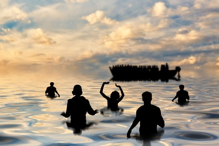 Refugees concept. Refugees swim to shore against the backdrop of boats Stock Photo