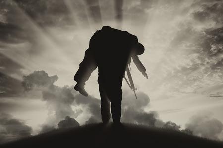 戦争と紛争の概念。煙の空の背景に負傷した兵士を運ぶ兵士