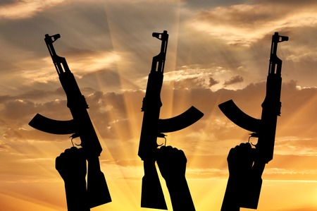 terrorists: Terrorists concept. Weapons in the hands of terrorists, on the sunset background