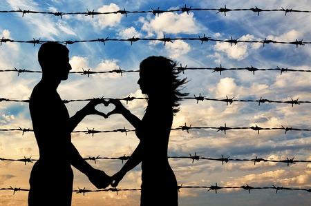 show hands: Los refugiados concepto. refugiados masculinos y femeninos muestran las manos símbolo del corazón en el fondo de la valla de alambre de púas