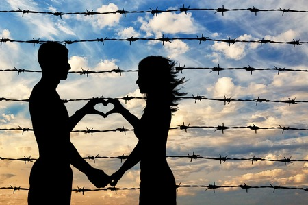 alzando la mano: Refugees concept. Male and female refugees show hands symbol heart on the background of the fence barbed wire