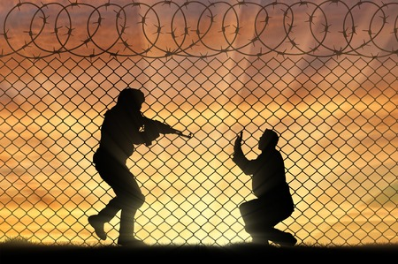 hostages: Terrorism concept. Terrorist attack on a peaceful man near the fence of barbed wire
