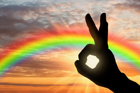 Gesture ok. Ok hand gesture against the backdrop of a rainbow sunset