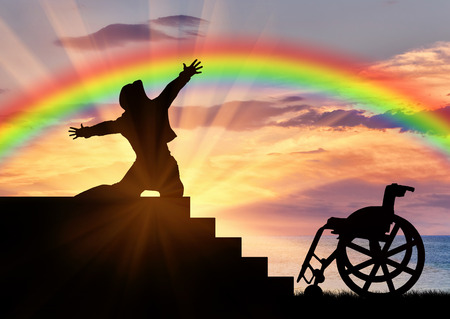 winner man: Disability. Happy disabled near the wheelchair is experiencing the joy of watching the sunset and rainbow