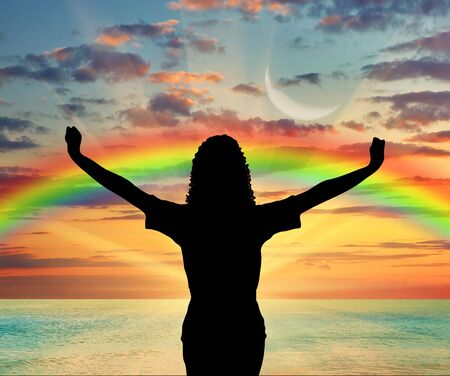 manos levantadas al cielo: Happiness and success. Happy woman with raised arms on a rainbow background and sea sunset