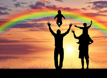 Gays and family. Pair of gay men and their children playing at sunset on the sea with a rainbow Imagens