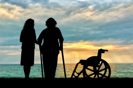 Silhouette of a disabled wheelchair near the peepers and near sea. The concept of a disabled person and the home for elderly Imagens