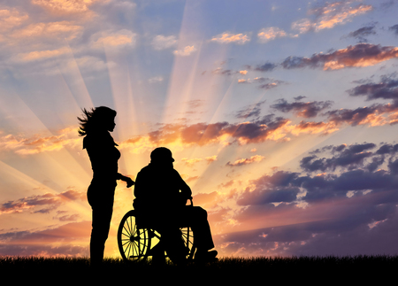Silhouette of a nurse caring for a disabled person in a wheelchair. Concept of caring for a disabled person and the house of aged