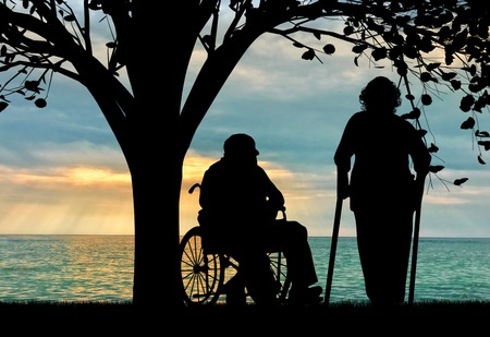 Silhouette of two people with disabilities. Disabled person in a wheelchair and on crutches resting under a tree by the sea