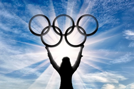 Olympic athlete raised his hands and holds Olympic rings on background of sun. Sport concept