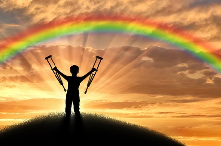 Child disabled with crutches on a hill on a background of a sunset rainbow. Concept of disability