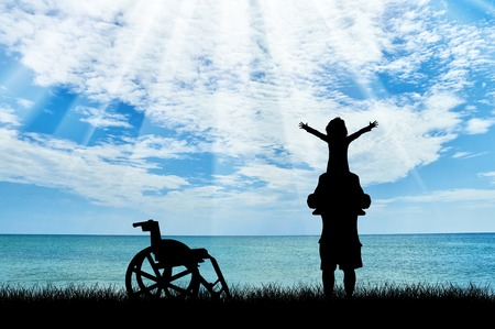 Happy disabled child on shoulders of dad and wheelchair near sea day. Concept happy child disabled Stock Photo