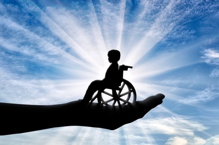 Disabled child in a wheelchair in a mans hand. Concept of care and help Stock Photo