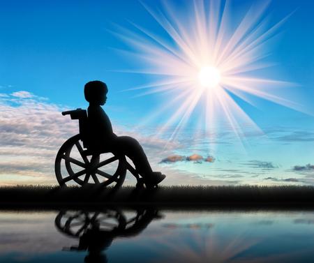 niños discapacitados: El muchacho en silla de ruedas y la reflexión en el agua día. Concepto de los niños con discapacidad Foto de archivo