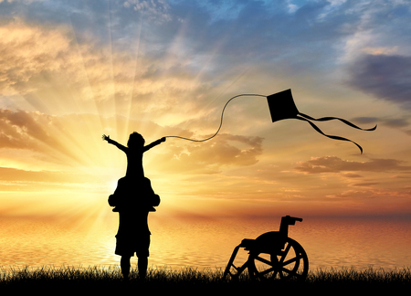 Happy disabled child on shoulders of dad playing with kite and wheelchair near sea sunset. Disabled children concept Stock Photo