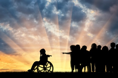 misunderstanding: Disabled child in a wheelchair crying and children chased him sunset. Concept disabled child Stock Photo