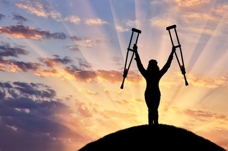 perseverance: Happy disabled raised his hands with his crutches on hill sunset. Concept happy disabled