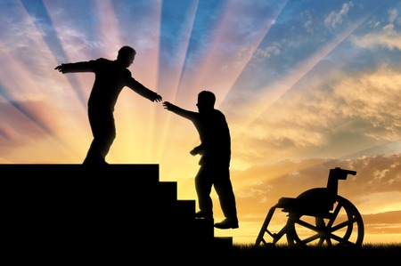 Man gives helping hand to disabled person in wheelchair sunset. Concept assistance disabled persons Фото со стока
