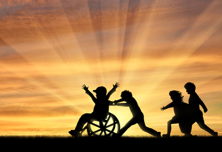 Happy boy in wheelchair playing with children sunset. Concept happy child disabled