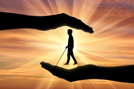 Association of blind people with disabilities under protection in hands sunset. Concept help blind people disabilities