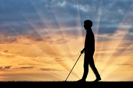 Blind man with cane disabled person goes on street sunset. Concept help blind people disabilities