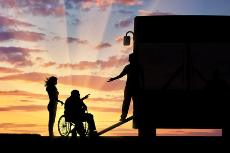 Disabled person in wheelchair to help climb the ramp in bus sunset. Concept help disabilities