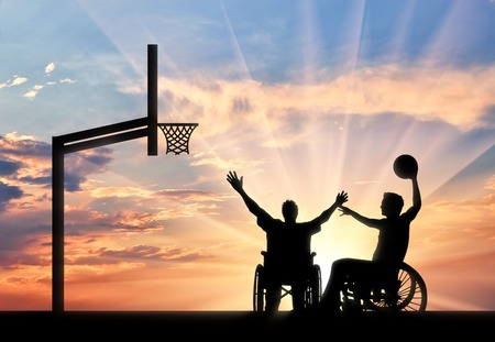 Disabled paralympians in wheelchair play basketball on basketball court with ball sunset. Concept sport and willpower