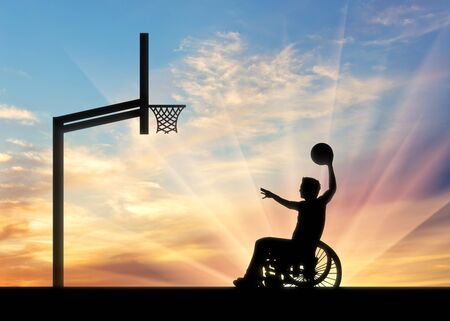 Paralympic disabled person in wheelchair rolls ball into basket sunset. Concept sport and willpower Stock Photo