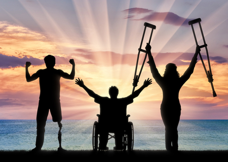 Three happy disabled with prosthesis and crutches and in wheelchair near sea. Concept happy disabled