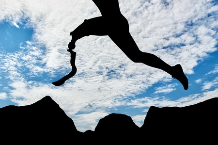 aspirational: Disabled athlete with prosthetic leg jumping over rocks on background of sky. Concept disability and sport Stock Photo