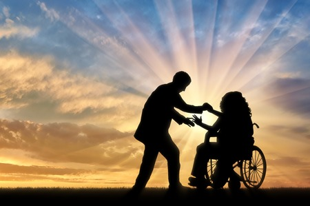 helps: Man helps woman in wheelchair to stand up sunset. Concept help disabled persons