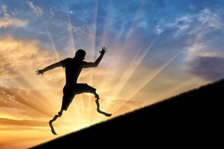 amputation: Disabled runner with prosthetic legs to rise up on background sunset . Concept disability and sport Stock Photo