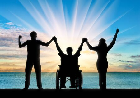 Disabled in wheelchair and healthy people holding hands on sea day. Concept happy disabled