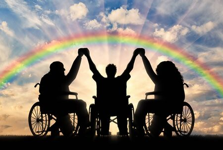unprotected: Disabled in wheelchair on rainbow background holding hands. Concept happy disabled