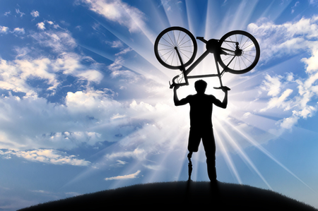 Disabled with prosthetic leg standing on hill and holding bicycle over his head day. Concept disabled and sport